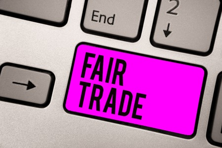 Text sign showing Fair Trade. Conceptual photo Small increase by a manufacturer what they paid to a producer Keyboard purple key Intention create computer computing reflection document Фото со стока
