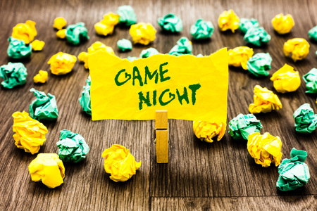 Writing note showing Game Night. Business photo showcasing event in which folks get together for the purpose of getting laid Clothespin holding yellow note paper crumpled papers several tries