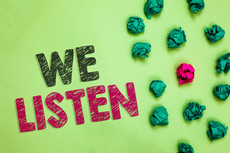 Text sign showing We Listen. Conceptual photo Group of people that is willing to hear anything you want to say Crumpled wrinkled papers one different pink unique special green background Stok Fotoğraf