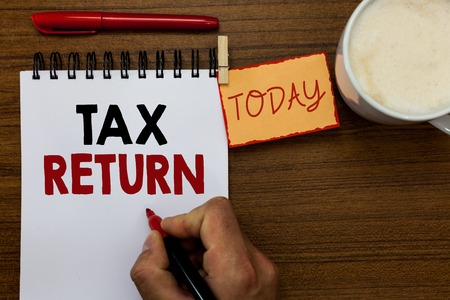 Text sign showing Tax Return. Conceptual photo which taxpayer makes annual statement of income circumstances Man holding marker notebook clothespin reminder wooden table cup coffee
