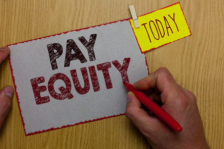 Word writing text Pay Equity. Business concept for eliminating sex and race discrimination in wage systems Man holding marker paper clothespin reminder express ideas wooden table Stock Photo