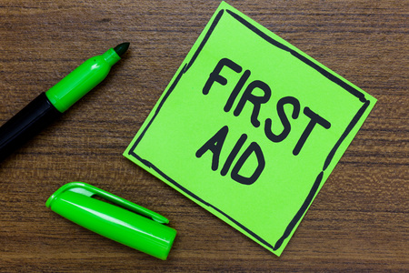 Conceptual hand writing showing First Aid. Business photo showcasing Practise of healing small cuts that no need for medical training Green Paper Communicate ideas Marker Wooden background
