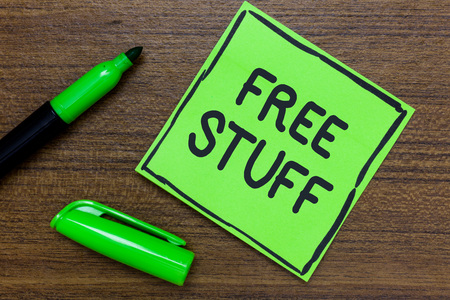 Conceptual hand writing showing Free Stuff. Business photo showcasing Any thing that you can have in a store that is not being paid Green Paper Communicate ideas Marker Wooden background