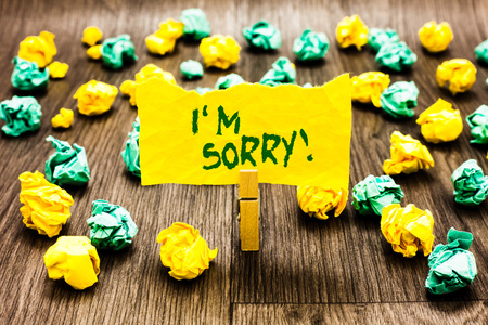 Writing note showing I am Sorry. Business photo showcasing To ask for forgiveness to someone you unintensionaly hurt Clothespin holding yellow note paper crumpled papers several tries
