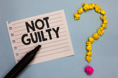 Word writing text Not Guilty. Business concept for someone is innocent didnt commit specific crime He free Paper marker crumpled papers forming question mark wooden background