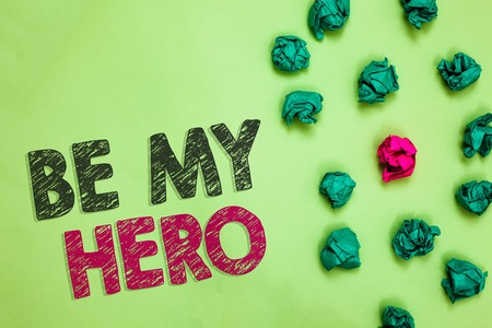 Text sign showing Be My Hero. Conceptual photo Request by someone to get some efforts of heroic actions for him Crumpled wrinkled papers one different pink unique special green background Banco de Imagens