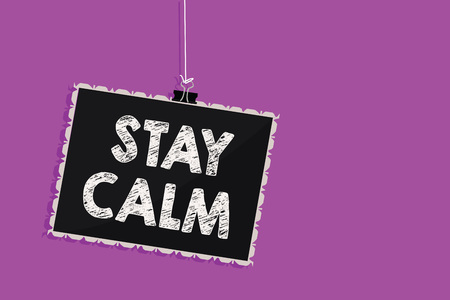 Text sign showing Stay Calm. Conceptual photo Maintain in a state of motion smoothly even under pressure Hanging blackboard message communication information sign purple background Stock Photo