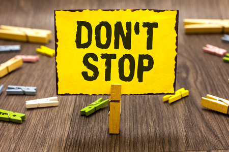 Text sign showing Don t not Stop. Conceptual photo Continue what had been doing without rendering a delay Clothespin holding yellow paper note several clothespins wooden floor