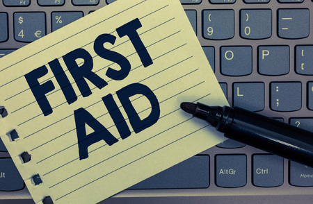 Conceptual hand writing showing First Aid. Business photo showcasing Practise of healing small cuts that no need for medical training Notebook paper keyboard Inspiration computer black marker