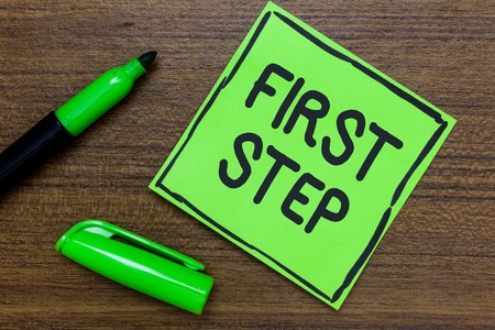 Conceptual hand writing showing First Step. Business photo showcasing Pertaining to the start of a certain process or beginning Green Paper Communicate ideas Marker Wooden background
