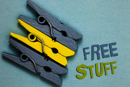 Conceptual hand writing showing Free Stuff. Business photo text Any thing that you can have in a store that is not being paid Gray yellow vintage clothespins clear background Holding things Stock Photo