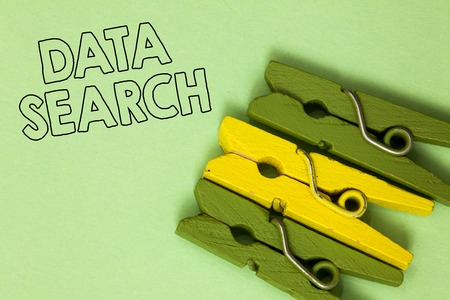 Text sign showing Data Search. Conceptual photo gathers and reports information contains specified terms Three green yellow vintage clothespins clear background Holding things