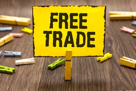 Text sign showing Free Trade. Conceptual photo The ability to buy and sell on your own terms and means Clothespin holding yellow paper note several clothespins wooden floor