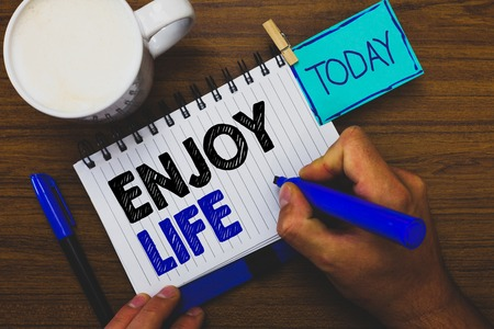 Word writing text Enjoy Life. Business concept for Any thing, place,food or person, that makes you relax and happy Man holding marker notebook clothespin reminder wooden table cup coffee Stock Photo