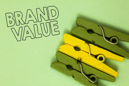 Text sign showing Brand Value. Conceptual photo company generates from product with recognizable for its names Three green yellow vintage clothespins clear background Holding things Banco de Imagens - 106533211