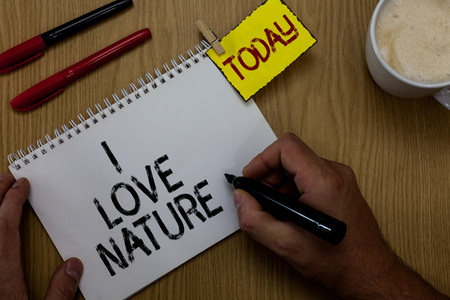 Handwriting text writing I Love Nature. Concept meaning Enjoy the natural environment Preservation Protect ecosystem Man holding marker notebook clothespin reminder wooden table cup coffee Imagens
