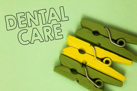 Text sign showing Dental Care. Conceptual photo maintenance of healthy teeth or to keep it clean for future Three green yellow vintage clothespins clear background Holding things