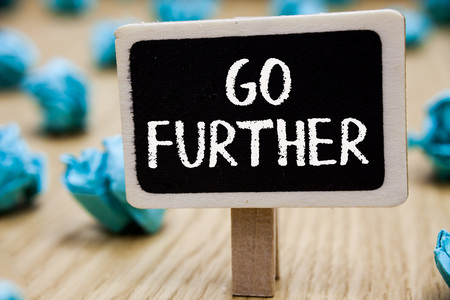 Text sign showing Go Further. Conceptual photo To move to a greater distance or overcome your limitations Blackboard crumpled papers several tries mistake not satisfied wooden floor