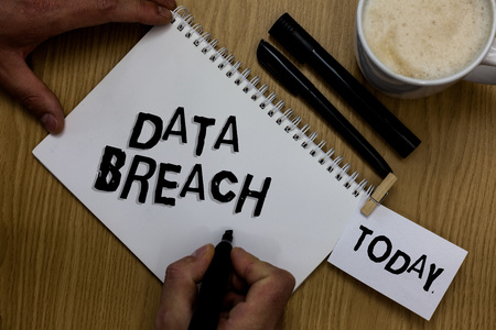 Writing note showing Data Breach. Business photo showcasing security incident where sensitive protected information copied Man holding marker notebook clothepin reminder wooden table cup coffee