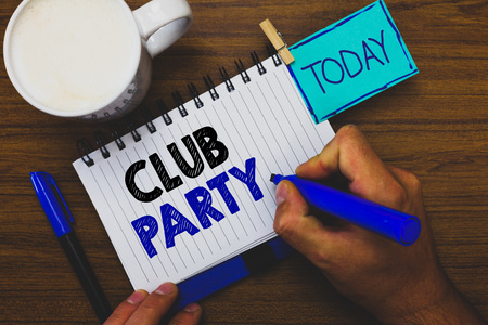Word writing text Club Party. Business concept for social gathering in a place that is informal and can have drinks Man holding marker notebook clothespin reminder wooden table cup coffee Stock Photo