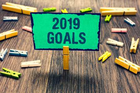 Word writing text 2019 Goals. Business concept for A plan to do for something new and better for the coming year Clothespin holding green paper note several clothespins wooden floor