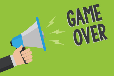 Writing note showing Game Over. Business photo showcasing A situation in a particular sport that reach his finals or ending Man holding megaphone loudspeaker green background message speaking Stock Photo