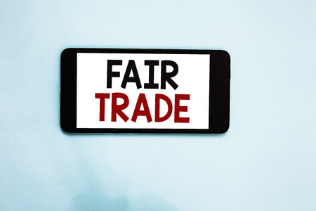 Text sign showing Fair Trade. Conceptual photo Small increase by a manufacturer what they paid to a producer Cell phone white screen over light blue background text messages apps Фото со стока