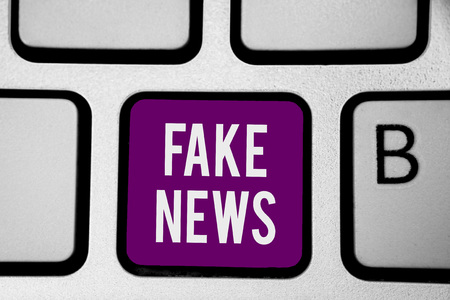 Writing note showing Fake News. Business photo showcasing Giving information to people that is not true by the media Keyboard purple key Intention computer computing reflection document 写真素材