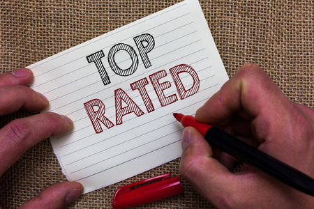 Writing note showing Top Rated. Business photo showcasing The high amount of a charge or payment based on calculation Mans hand hold white paper with symbolic letter jute sack background