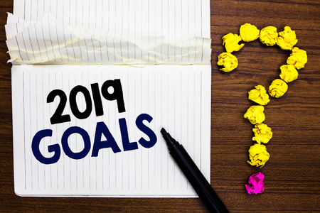 Writing note showing 2019 Goals. Business photo showcasing A plan to do for something new and better for the coming year Notebook marker crumpled paper forming question mark wooden background Banco de Imagens
