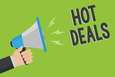 Writing note showing Hot Deals. Business photo showcasing An agreement through which one of the paties is offered and accept Man holding megaphone loudspeaker green background message speaking