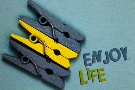 Conceptual hand writing showing Enjoy Life. Business photo text Any thing, place,food or person, that makes you relax and happy Gray yellow vintage clothespins clear background Holding things Stock Photo
