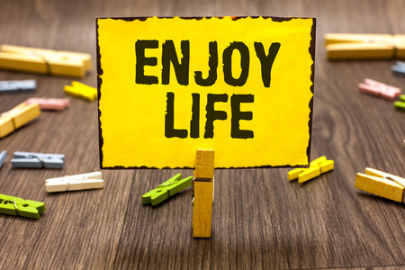 Text sign showing Enjoy Life. Conceptual photo Any thing, place,food or person, that makes you relax and happy Clothespin holding yellow paper note several clothespins wooden floor