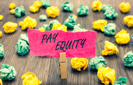 Writing note showing Pay Equity. Business photo showcasing eliminating sex and race discrimination in wage systems Clothespin holding pink note paper crumpled papers several tries