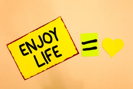 Conceptual hand writing showing Enjoy Life. Business photo text Any thing, place,food or person, that makes you relax and happy Yellow paper reminder equal sign heart sending romantic feelings