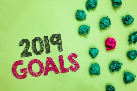Text sign showing 2019 Goals. Conceptual photo A plan to do for something new and better for the coming year Crumpled wrinkled papers one different pink unique special green background Stock Photo