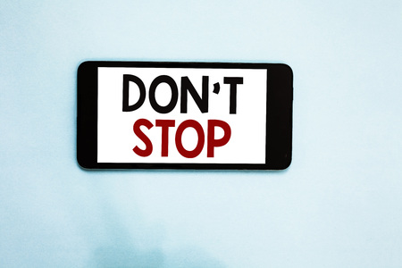 Text sign showing Don t not Stop. Conceptual photo Continue what had been doing without rendering a delay Cell phone white screen over light blue background text messages apps Foto de archivo