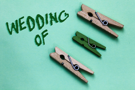Text sign showing Wedding Of. Conceptual photo announcing that man and woman now as married couple forever Three brown green vintage clothespins clear background Holding things