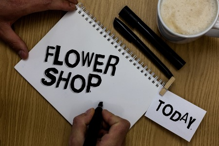 Writing note showing Flower Shop. Business photo showcasing where cut flowers are sold with decorations for gifts Man holding marker notebook clothepin reminder wooden table cup coffee