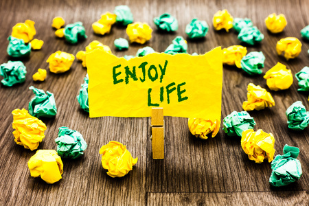 Writing note showing Enjoy Life. Business photo showcasing Any thing, place,food or person, that makes you relax and happy Clothespin holding yellow note paper crumpled papers several tries 스톡 콘텐츠