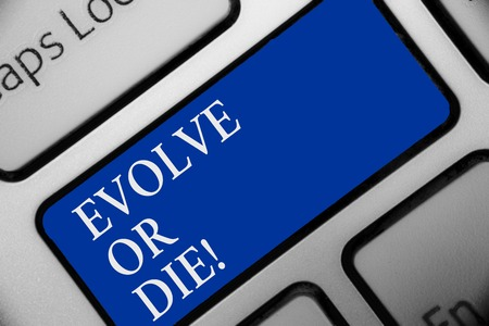 Text sign showing Evolve Or Die. Conceptual photo Necessity of change grow adapt to continue living Survival Keyboard blue key Intention create computer computing reflection document Stock Photo