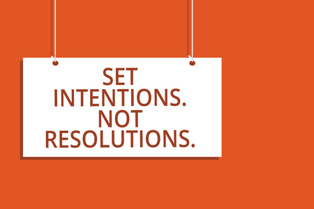 Word writing text Set Intentions. Not Resolutions.. Business concept for Positive choices for new start achieve goals Hanging board message communication open close sign orange background