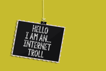 Handwriting text Hello I Am An ... Internet Troll. Concept meaning Social media troubles discussions arguments Hanging blackboard message communication information sign yellow background