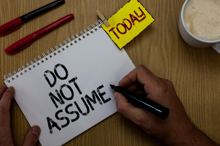 Handwriting text writing Do Not Assume. Concept meaning Ask first to avoid misunderstandings confusion problems Man holding marker notebook clothespin reminder wooden table cup coffee