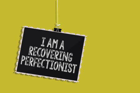 Handwriting text I Am A Recovering Perfectionist. Concept meaning Obsessive compulsive disorder recovery Hanging blackboard message communication information sign yellow background