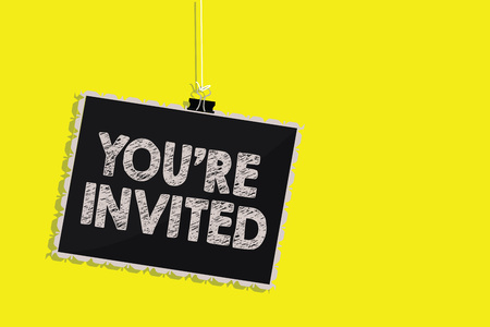 Writing note showing You re are Invited. Business photo showcasing Please join us in our celebration Welcome Be a guest Hanging blackboard message communication sign yellow background Stok Fotoğraf