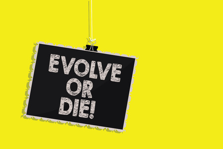 Writing note showing Evolve Or Die. Business photo showcasing Necessity of change grow adapt to continue living Survival Hanging blackboard message communication sign yellow background Stock Photo