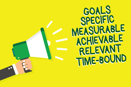Writing note showing Goals Specific Measurable Achievable Relevant Time Bound. Business photo showcasing Strategy Mission Man holding megaphone loudspeaker yelliw background speaking loud Imagens