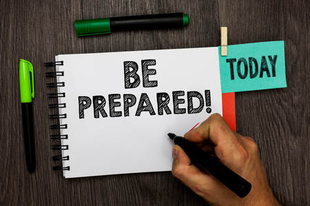Conceptual hand writing showing Be Prepared. Business photo showcasing Getting ready for whatever will happen Plan Ahead of time Man holding marker notebook reminder cup markers wood table Stock Photo