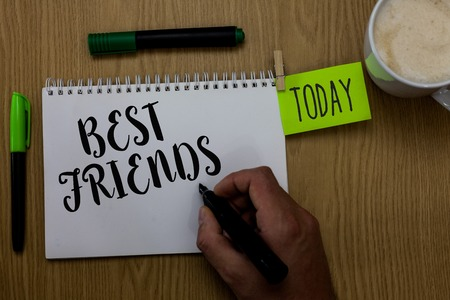 Writing note showing Best Friends. Business photo showcasing A person you value above other persons Forever buddies Man holding marker notebook clothepin reminder wooden table cup coffee